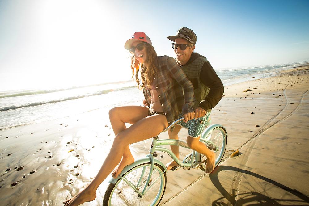 Young couple riding a cruiser bike on the beach in Encinitas, CA.