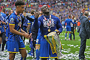 AFC Wimbledon striker Adebayo Akinfenwa (10) smiling with the trophy during the Sky Bet League 2 play off final match between AFC Wimbledon and Plymouth Argyle at Wembley Stadium, London, England on 30 May 2016.