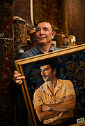 Albert Borokhim poses for a portrait inside Borokhim's Oriental Rugs on Monroe Street with a portrait of himself from 1973, Monday, April 24, 2017. Borokhim moved to the United States nearly fifty years ago and opened his Persian rug store in 1972.