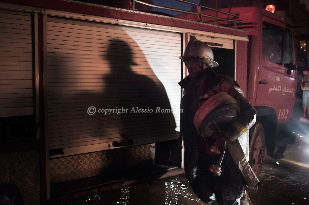 Gaza Strip, Gaza City:  A firefighter carries a fire hose as other colleagues try to extinguish a fire at a soap factory in Gaza City after was hit by an Israeli airstrike on August 10, 2012. ALESSIO ROMENZI