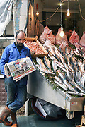 Fishmonger at a fish stall in a market reads a newspaper. Photographed in Istanbul, Turkey