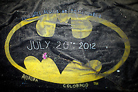 A Batman logo is covered with dirt left at the memorial to the movie theater shooting victims in Aurora July 25, 2012. First responders got their first look at the growing memorial today.   REUTERS/Rick Wilking (UNITED STATES)