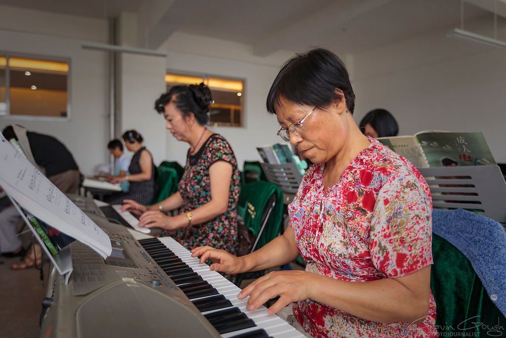A woman learning to play the piano on an electronic keyboard during a class at a University of the Third Age (U3A).