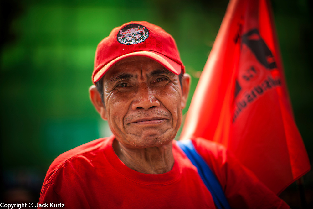 """10 DECEMBER 2012 - BANGKOK, THAILAND:   A Red Shirt protestor on Ratchadamnoen Avenue in Bangkok Monday. The Thai government announced on Monday, which is Constitution Day in Thailand, that will speed up its campaign to write a new charter. December 10 marks passage of the first permanent constitution in 1932 and Thailand's transition from an absolute monarchy to a constitutional monarchy. Several thousand """"Red Shirts,"""" supporters of ousted and exiled Prime Minister Thaksin Shinawatra, motorcaded through the city, stopping at government offices and the offices of the Pheu Thai ruling party to present demands for a new charter.       PHOTO BY JACK KURTZ"""