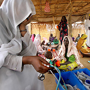 June 10, 2004 - A weary nurse takes a break at the MSF-Holland (Doctors Without Borders) feeding center,where mothers wait with their malnourished children, in the Kalma IDP camp in Darfur. Over 300 children suffering from severe malnutrition have arrived at the camp over the past weeks. CARE, an international aid organization, is feeding 20,000 IDP's at Kalma camp and some 400,000 IDP's throughout Darfur, Sudan.  Photo by Evelyn Hockstein/CARE