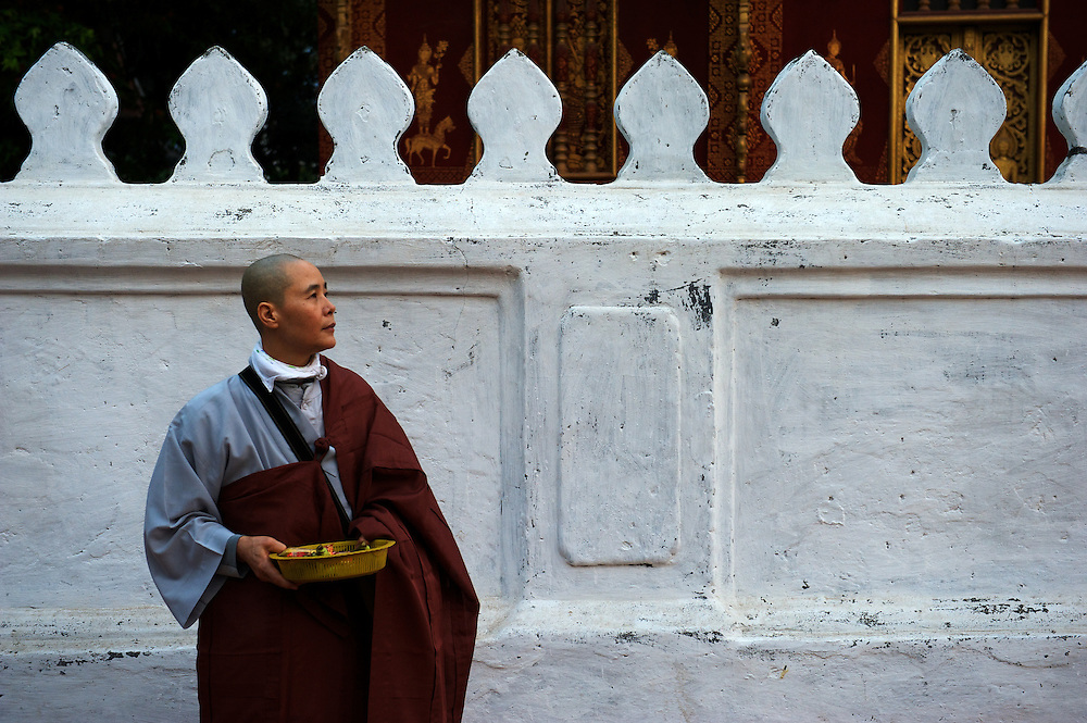 A Chinese pilgrim nun waits outside a wat to give alms to local Laotian monk novices,Luang Prabang, Mekong River, Laos