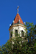 The bell tower or Church Spire of The Cathedral-Basilica of St. Augustine, Florida stands above the trees, set against the backdrop of a deep blue sky.