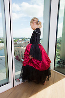 Full length of girl in vampire costume looking out through window at home