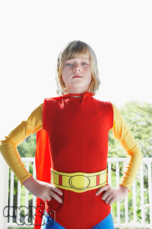 Portrait of young boy (7-9) in superhero costume hands on hip