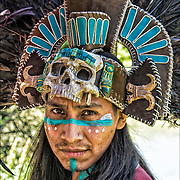 Head and shoulders of Aztec dancer wearing his head dress and regalia at Drums Along the Hudson, in Inwood Hill Park, NYC.<br /> <br />  Every movement in the choreography of dance has a specific meaning. Squats and serpentine movements represent fertility, steps firmly on the ground and planting land, air and turns the spirit, advanced steps and retroceded fire and water zigzagging steps. Always relation to the four elements is found. water, fire, wind, earth.<br /> <br /> Also this number is prevalent in Mexican culture as it also represents the four directions, north, south, east, west among other interpretations. Azteca dance origins / Mexihca in