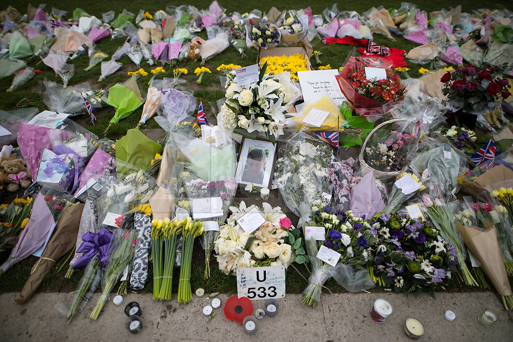 © Licensed to London News Pictures . 27/03/2017 . London , UK . A wreath of white roses sent by British Prime Minister Theresa May (bottom centre) amongst flowers and tributes in Parliament Square opposite Parliament in Westminster , in response to Khalid Masood's terrorist attack and the killing of PC Keith Palmer . Photo credit: Joel Goodman/LNP