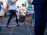 """04 MARCH 2015 - BANGKOK, THAILAND: People in a procession around the """"wiharn,"""" or prayer hall, pass a woman in a wheelchair at Wat Benchamabophit on Makha Bucha Day. Makha Bucha Day is an important Buddhist holy day and public holiday in Thailand, Cambodia, Laos, and Myanmar. Many people go to temples to perform merit-making activities on Makha Bucha Day. Wat Benchamabophit is one of the most popular Buddhist temples in Bangkok.    PHOTO BY JACK KURTZ"""