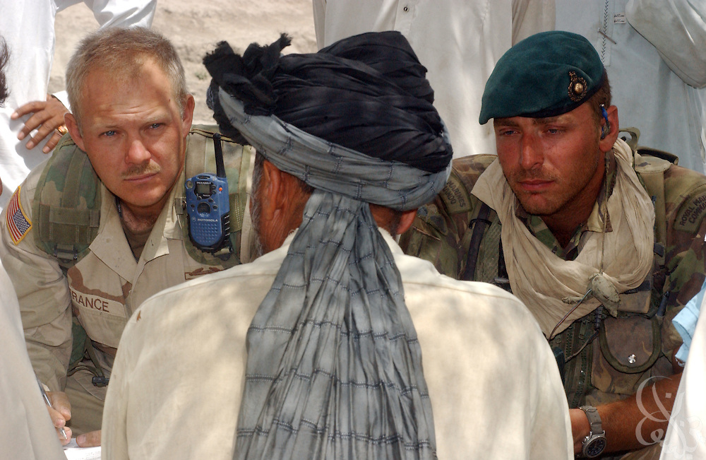 A U.S. Army Civil Affairs commander (l) and his British Royal Marine counterpart speak with a village elder during a June 18, 2002 humanitarian mission in southeastern Afghanistan.