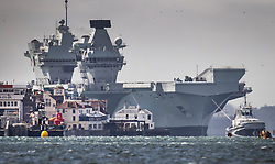 © Licensed to London News Pictures. 02/07/2020. Portsmouth, UK. Royal Navy aircraft carrier HMS Queen Elizabeth towers over Old Portsmouth (L) as she enters Portsmouth harbour. The 65,000 tonne supercarrier has been at sea for 10 weeks conducting trials of the new F35 Lightening fighter jets ahead of her first operational mission in 2021. Photo credit: Peter Macdiarmid/LNP