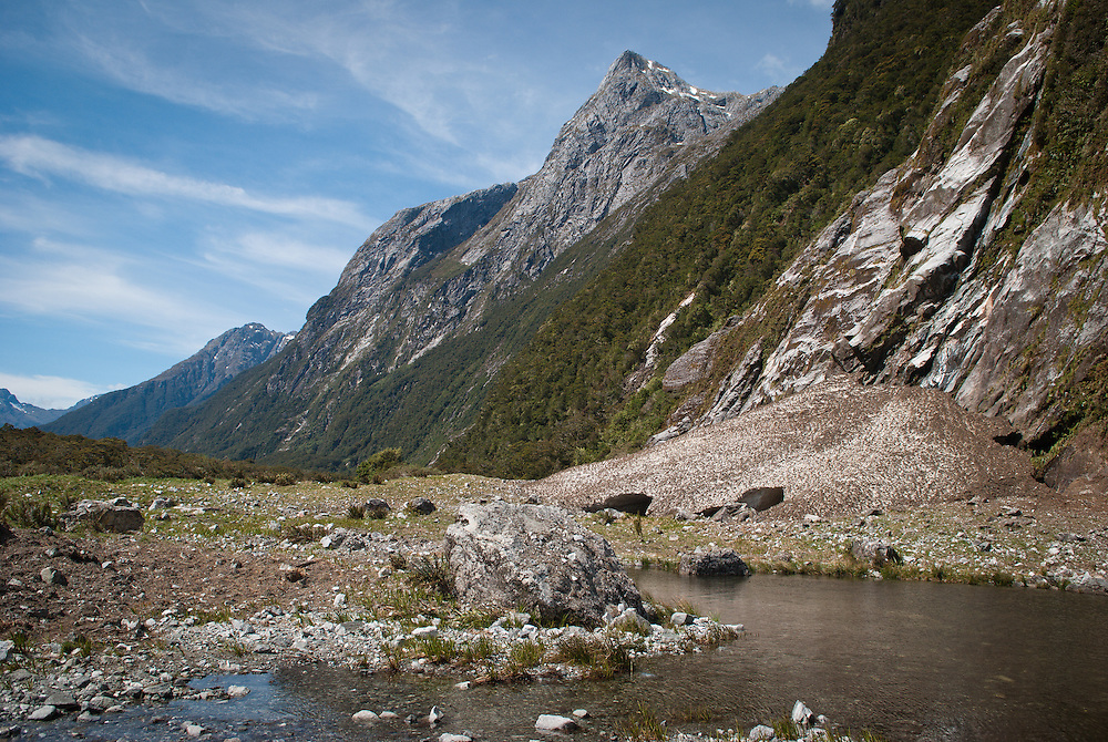 Residual snow and rocks form a pile near the river at the base of a deforested mountainside, Clinton Canyon, Milford Track, New Zealand