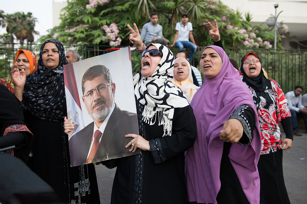 Supporters of ousted President Morsi hold a poster with the face of Morsi during a rally in front of the Republican Guard Headquarters in Cairo, Egypt, July 5, 2013