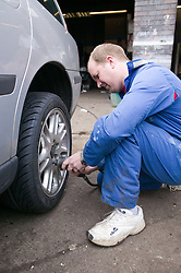 Car mechanic taking the wheel off a car,