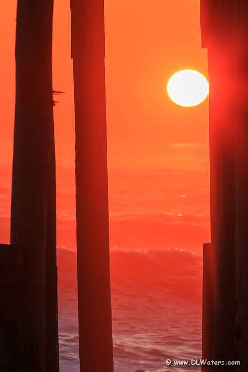 Orange sunrise through the pilings and over the surf at Kitty Hawk Pier on the Outer Banks of NC.