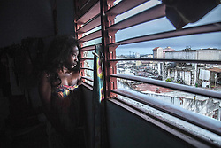 November 23, 2016 - Havana, Cuba - A jinetera (illegal or semi-legal economic activities related to prostitution) in her rent room watching Havana  (Credit Image: © Alvaro Fuente/NurPhoto via ZUMA Press)