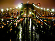 The Brooklyn Bridge illuminated by night on a rainy day, Brooklyn, New York.