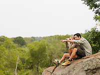 Man and woman sitting on rock looking at view man pointing