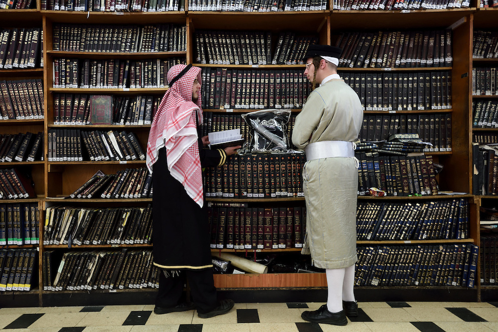 A Jewish man waering an Arab costume holds a Jewish prayer book while talkin to another Jewish man during Purim Holiday celebrations in the Ultra-Orthodox Jewish neighbourhood of Mea Shearim in Jerusalem, on March 6, 2015. The Jewish holiday of Purim commemorates the salvation of the Jews living with in the borders of the ancient Persian Empire. Purim customs include food gifts, charity, wearing costumes and drinking heavily.