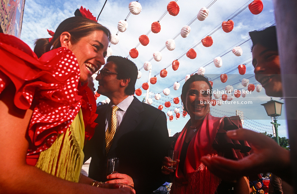 Spanish men and women party in mixed company at a private party outside a marquee called a Caseta during the annual Feria de Abril, on 11th June 1999, in Seville, Andalucia, Spain. Rows of temporary marquee tents, or casetas, host families, corporations and friends into the late hours during the April Fair which begins begins two weeks after the Semana Santa, or Easter Holy Week in the Andalusian capital.