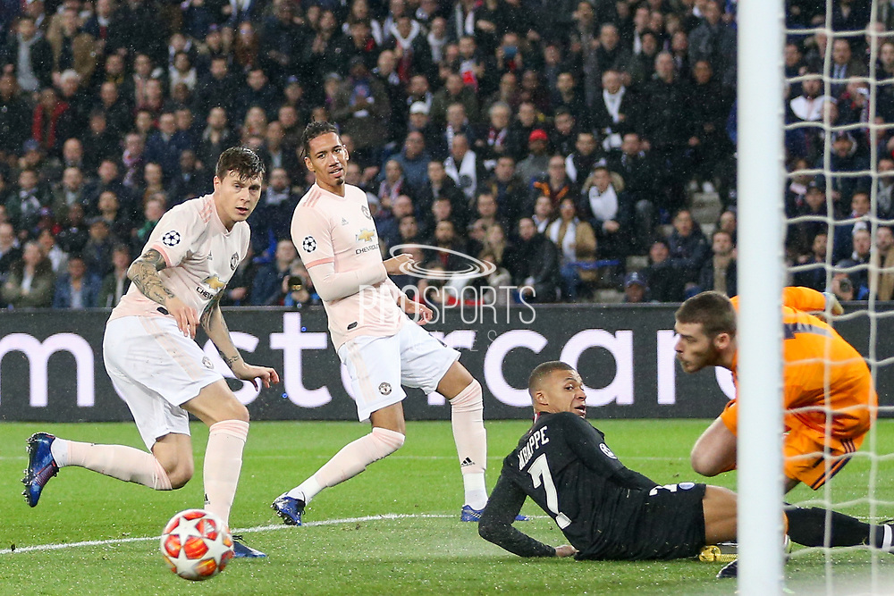 Kylian Mbappe of Paris Saint-Germain missed attempt at goal with Manchester United Defender Victor Lindelof and Manchester United Defender Chris Smalling looking on during the Champions League Round of 16 2nd leg match between Paris Saint-Germain and Manchester United at Parc des Princes, Paris, France on 6 March 2019.