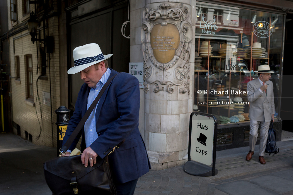 A gentleman wearing a Fedora hat searches his shoulder bag while walking past Laird Hatters where another man stands in a Panama, on the Strand, on 5th July 2017, in central London, England.
