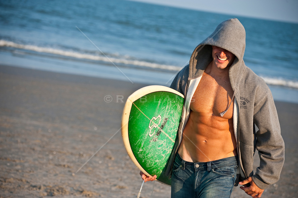 Surfer with an open sweat shirt and his surferboard
