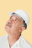 Senior man with hardhat looking up over yellow background