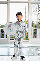 Portrait of young boy (5-6) posing in aluminum foil knight costume indoors