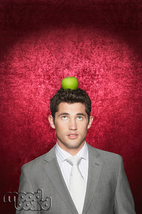 Man with apple on head against red velvet background