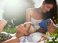 Women in meadow one reading book