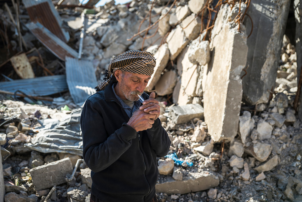 Kasim lights a cigarette outside the remains of his family home in the old city. He smokes 100 cigarettes per day, and made his own cigarettes from tea and vine leaves during ISIS' occupation of the city when smoking was forbidden. <br />