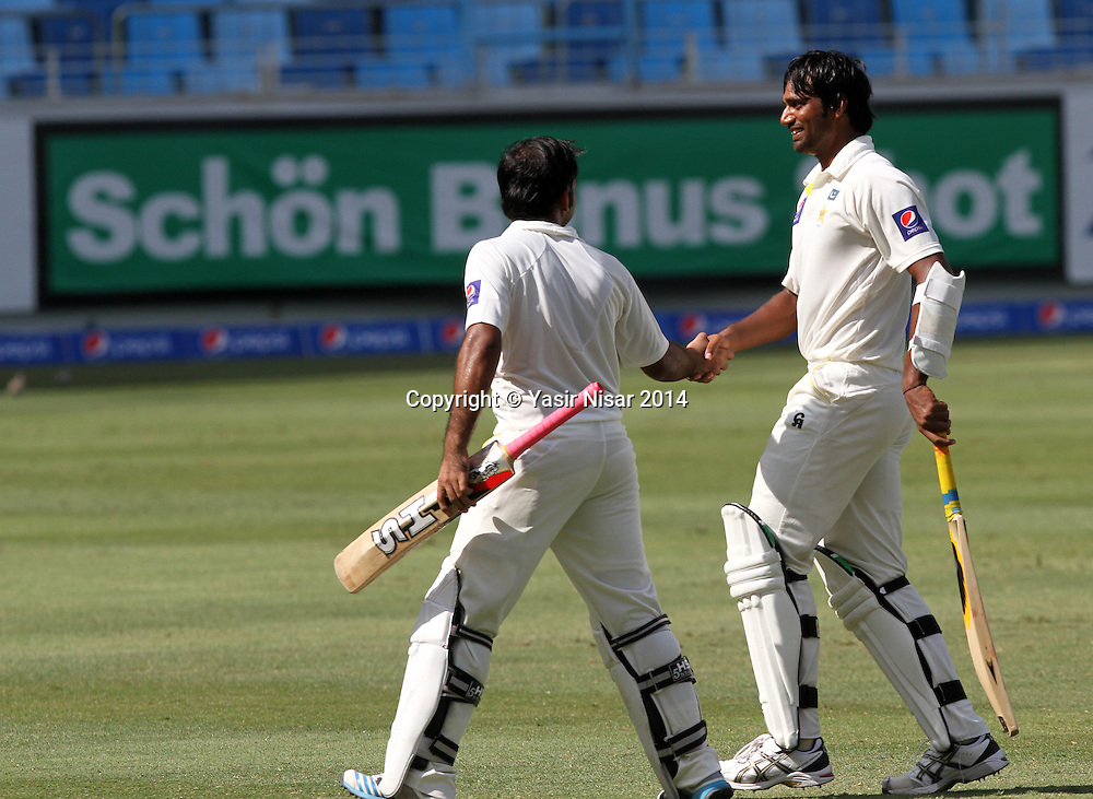 Pakistan vs New Zealand, 20 November 2014 <br /> Pakistani batsman Sarfraz Ahmed and Rahat Ali walks out of the ground after completing their first innings on the forth day of second test in Dubai