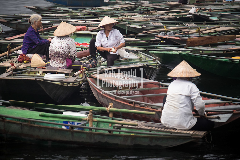 A group of women amongst the many other boats lined along the quayside at Tam Coc. Approximately 1300 people work at this location, and share the job of rowing  visitors along the 5km boat ride up the river surrounded by spectacular limestone karst scenery.