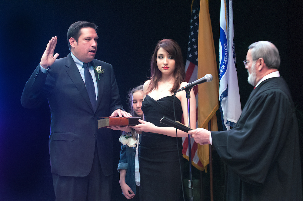 em031014k/a1/Santa Fe Mayor Javier Gonzales, left, with his daughters Cadence, 9, and Cameron, 15, is sworn in by retired New Mexico Supreme Court Justice Patricio Serna, Monday March 10, 2014. Eddie Moore/Albuquerque Journal