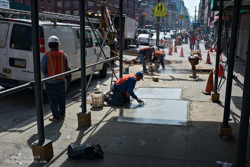 Workers repairing sidewalk, New York, NY, US