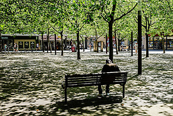 A man sits in dappled sunlight in Basildon Town Centre. Essex