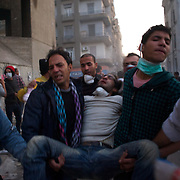 People carry an injured protestor during violent clashes with the security forces in central Cairo.