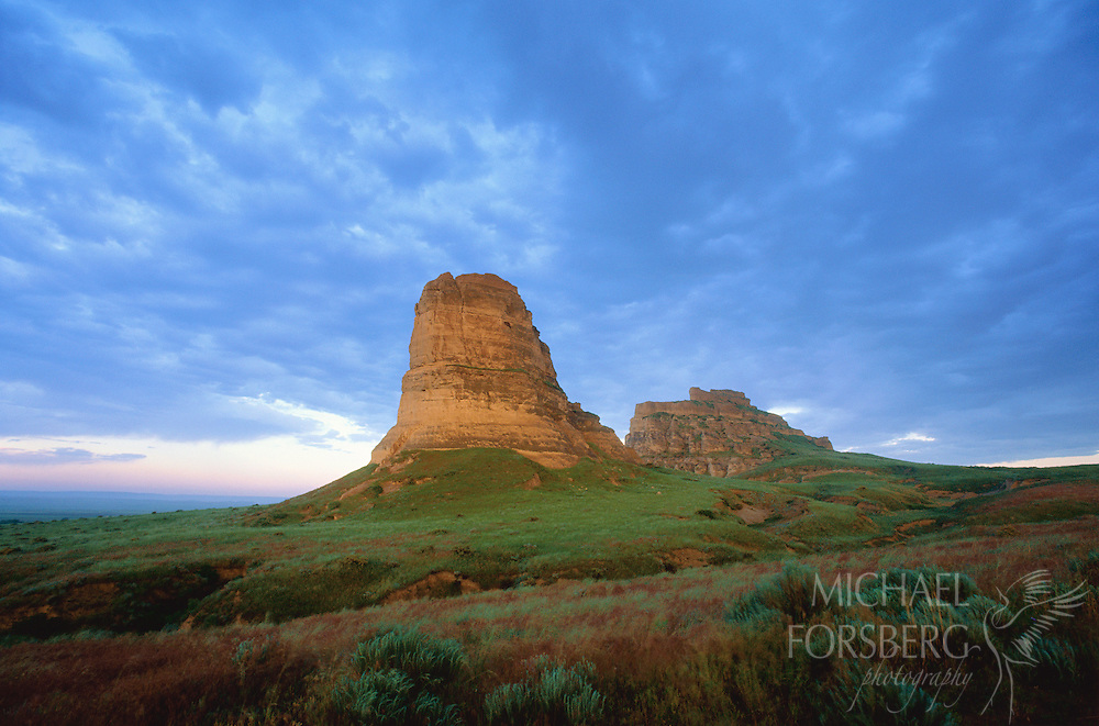 Courthouse & Jail Rock- Nebraska Panhandle.  Dawn's first light strikes Courthouse and Jail rocks shortly before an early June thundershower. The scene appears just as it likely did for pioneers moving westward 150 years ago. Courthouse and Jail rocks were two of the first landmarks met by westward travelers on the Oregon Trail in the North Platte River valley in western Nebraska. Several miles to the west, they would encounter Chimney Rock and Scotts Bluff.
