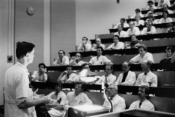 Nederland, Nijmegen, 15-9-1989Een arts bespreekt mert een aantal collega's, medisch specialisten, een casus, patient, in een collegezaal,hoorzaal, om gezamelijk tot een diagnose of behandelplan te komen.