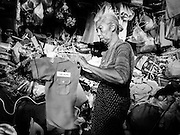 """08 FEBRUARY 2017 - BANGKOK, THAILAND: A woman folds her children's laundry in her home in Pom Mahakan. More than 40 families still live in Pom Mahakan, a slum community in a 19th century fort in Bangkok. City officials are trying to move them out of the fort but members of the community refuse to leave. NGOs and historic preservation organizations are working with the community to help them find a way to stay. After several deadlines passed, residents were told that they have to leave by the end of February. They submitted another proposal to the city this week to turn their community into a """"living heritage museum"""" and hope to get the eviction deadline extended until late March.       PHOTO BY JACK KURTZ"""