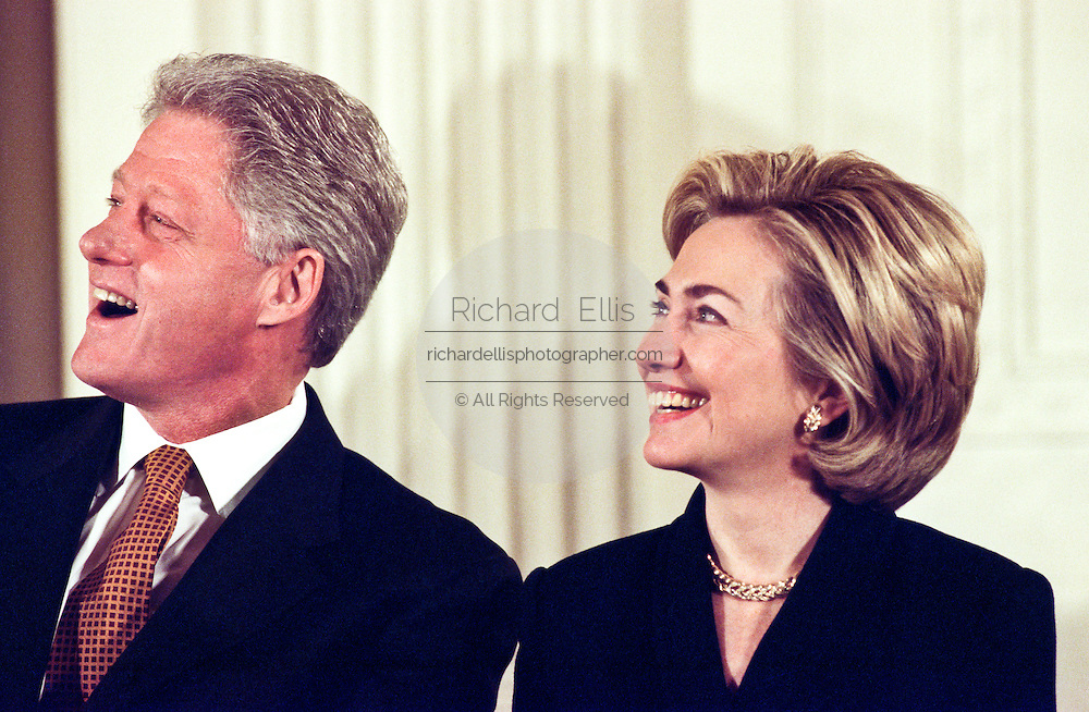 US President Bill Clinton and First Lady Hillary Clinton laugh as US Senator Chuck Robb, makes a joke about Mrs. Clinton's speculated run for the US Senate seat in New York, soon to be vacated by Senator Daniel Patrick Moynihan during a White House event February 17, 1999 in Washington, DC.