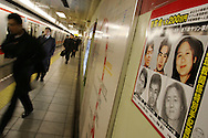 "AUM SHINRIKYO CULT  CRIMINALS. Police ""wanted"" poster for members of Aum Shinrikyo hangs on the platform wall on the Marunouchi subway line, one of the train lines attacked in the Sarin attack. Left to right the criminals are Hirata Makoto (left), Takahashi Katsuya (centre), Kikuchi Naoko (right). Takahashi and Kikuchi are ""wanted"" for taking part in the 1995 Tokyo underground sarin gas attack by Aum Shinrikyo Supreme Truth Cult, in Tokyo, Japan"