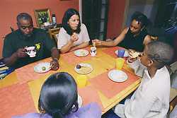 Mother and father sitting around dinner table with teenage son and daughters eating lunch,