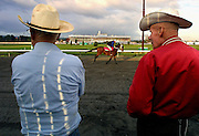 Ike Damm and Ted Nonamaker, both horse owner/trainers, watch as their animals take laps on the newly laid surface at the Portland Meadows race track. The late start of this season may shorten race lengths for a while as the horses work to reach peak condition.