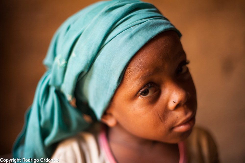 Latifa, 8, poses for a photograph at her home in Saran Maradi, Niger.<br /> Her grandmother Delou Ibrahim, 70, has four children and suffered the loss of nine. She has about 40 grandchildren, 16 of which live with her. <br /> &quot;I've seen several crises. The famine in 1984 was the hardest. Rains were very weak. The stems of millet came out but the spikes gave no grain - nothing,&quot; she recalls. &quot;Two years ago at least there were people who harvested millet, but this year the crops have been worse because of the drought and the leaf miners.&quot; Delou's last crop was 30kg, which only provided food for about two days.<br /> Delou and her family receive cash from CARE. &quot;I get to buy cereal to feed my family, particularly my grandchildren.&quot; They have two daily meals, porridge in the morning and sorghum paste in the evening.