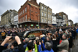 © Licensed to London News Pictures. 31/03/2018. Cambridge, UK.  The funeral procession leaves the church surrounded by mourners and members of the public. The funeral of Stephen Hawking at Church of St Mary the Great in Cambridge, Cambridgeshire. Professor Hawking, who was famous for ground-breaking work on singularities and black hole mechanics, suffered from motor neurone disease from the age of 21. He died at his Cambridge home in the morning of 14 March 2018, at the age of 76. Photo credit: Ben Cawthra/LNP
